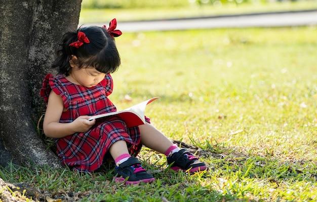Fille d'âge préscolaire asiatique lisant le livre sous l'arbre
