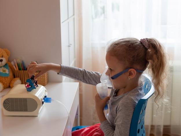 Fille d'âge préscolaire faisant l'inhalation avec le nébuliseur saison de la grippe