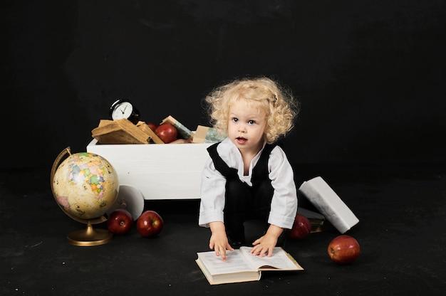 Fille d'âge préscolaire heureuse près du panier avec un livre, globe et horloge sur fond noir