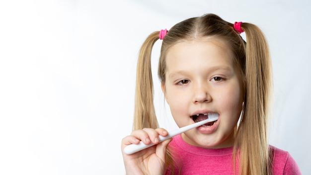 Fille d'âge préscolaire avec les premières incisives adultes et une brosse à dents. la dent de lait est tombée et une dent permanente pousse dans la bouche ouverte. concept d'hygiène dentaire.