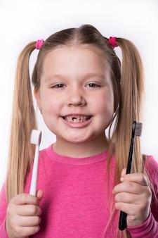 Fille d'âge préscolaire avec les premières incisives adultes et une brosse à dents