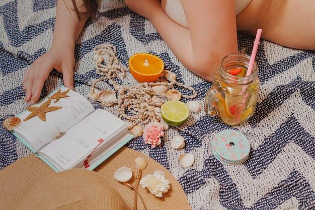 Fille avec agenda et boisson sur la plage