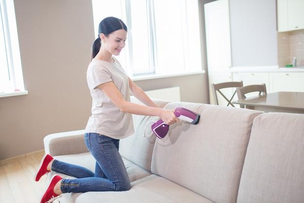 Une fille agréable et positive utilise un petit aspirateur sur le canapé. elle le nettoie. fille se tient à genoux sur le canapé.