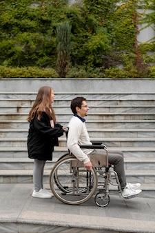 Fille aidant un homme handicapé voyageant dans la ville