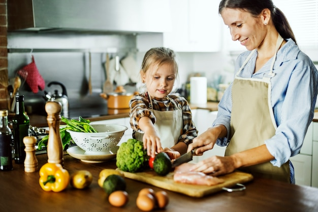 Fille aidant la mère dans la coupe de légumes