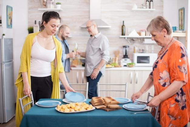 Fille aidant la mère dans la cuisine à mettre des assiettes sur la table pour le déjeuner en famille. pommes de terre rôties savoureuses sur table. homme senior tenant un verre à vin.