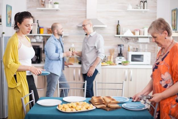 Fille aidant la mère dans la cuisine tout en préparant la table pour le déjeuner en famille. père et fils grillant des verres à vin.