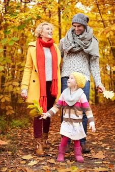 Fille aidant les parents à ramasser des feuilles