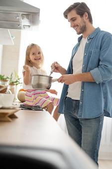 Fille aidant le père à préparer un repas dans la cuisine.
