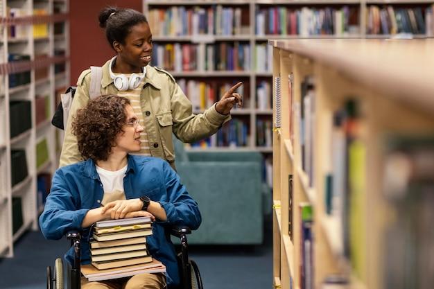 Fille aidant son collègue en fauteuil roulant à choisir un livre pour un projet