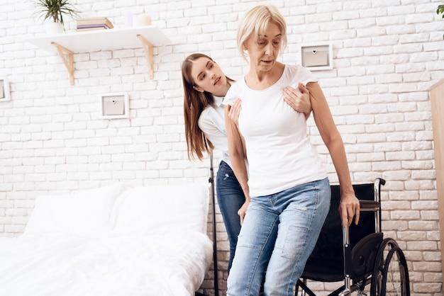 Une fille aide une femme à se mettre en fauteuil roulant