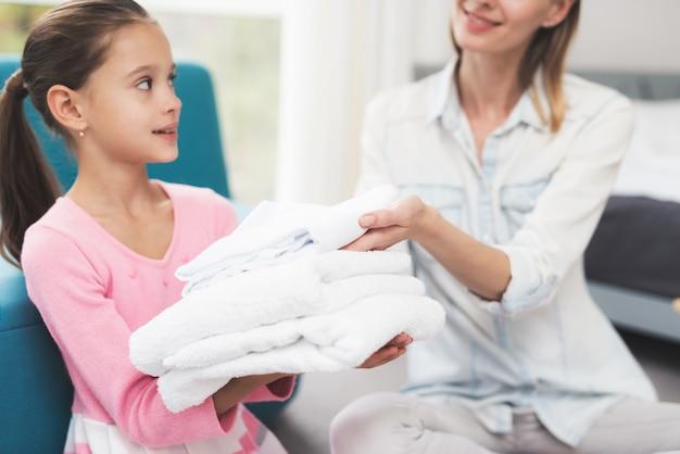 La fille aide la mère aux tâches ménagères.