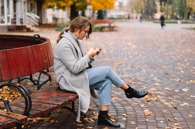 Fille à l'aide de téléphone dans le parc. concept technologique.