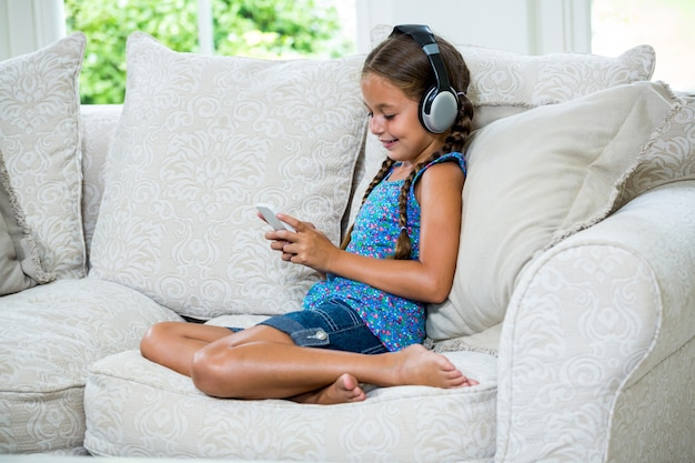 Fille à l'aide de téléphone portable tout en écoutant de la musique sur le canapé
