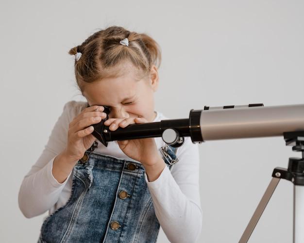 Fille à l'aide d'un télescope en classe