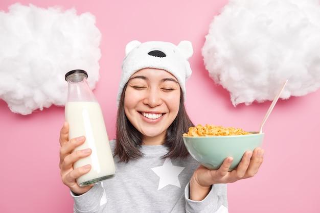 Fille aime bonjour prend son petit déjeuner mange des céréales avec du lait porte un pyjama et un chapeau mou préfère les aliments sains sourit largement a des dents blanches isolées sur rose