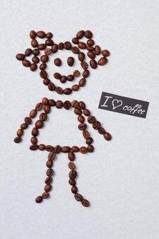 La fille aime le concept de café à plat. grains de café en forme de fille. surface isolée blanche.