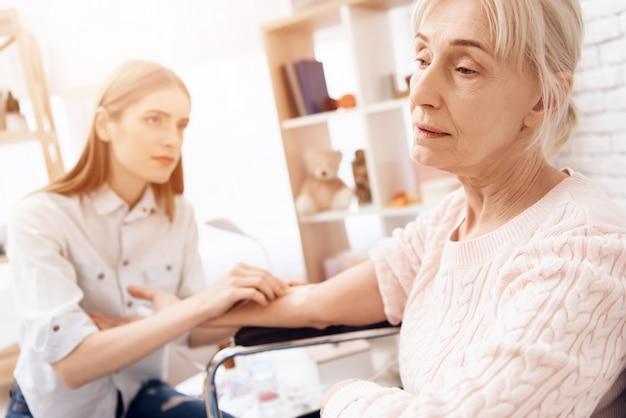 Une fille allaite une femme âgée en fauteuil roulant à la maison.