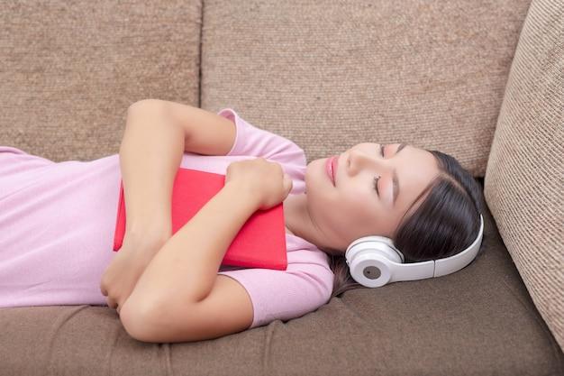 Fille allongée sur le canapé en écoutant de la musique et en lisant des livres.