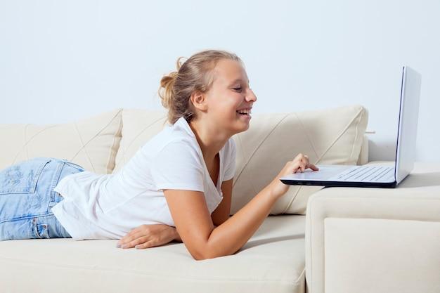 Fille allongée sur le canapé et regardant un ordinateur