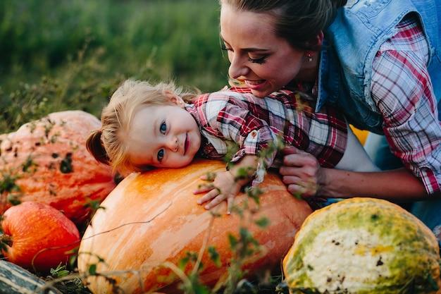 Fille allongée sur une citrouille et sa mère debout à côté