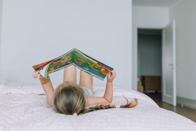 Fille allongée sur le lit et livre de lecture