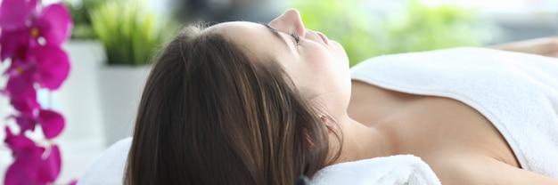 Fille allongée à la maison sous une serviette après le concept de spa de massage
