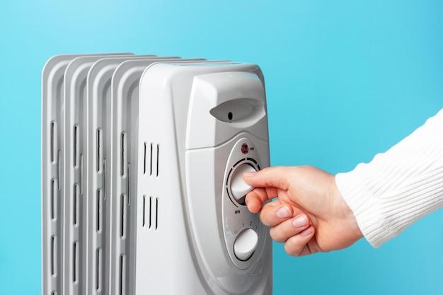 Fille allume le radiateur sur le fond bleu