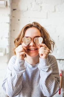 Fille à l'allure européenne tenant des biscuits en forme de coeur, amoureux, saint valentin, cuisson, cuisson