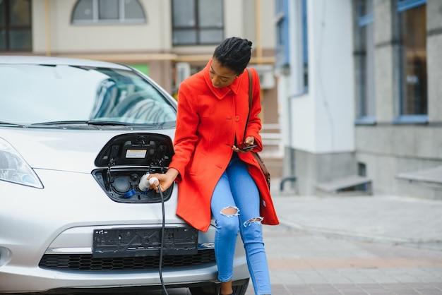 Fille américaine sur la station de charge de voitures électriques pendant la journée.