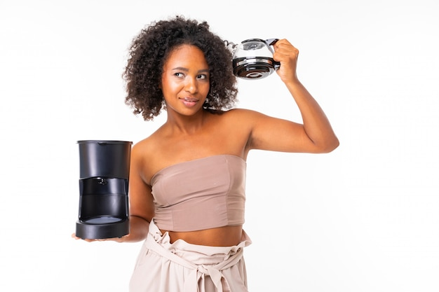 Fille américaine avec une tasse de café et une machine à café sur un mur blanc