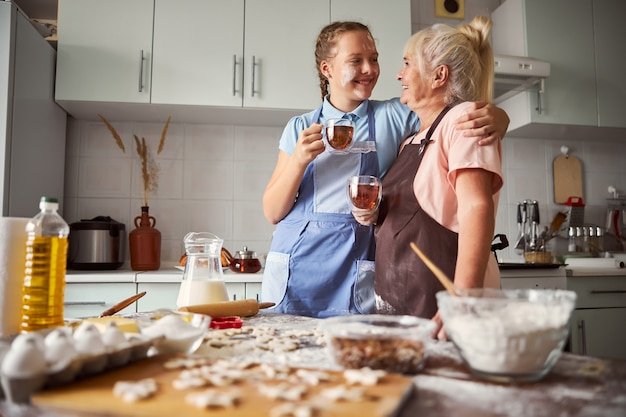 Fille amicale donnant à sa grand-mère un gros câlin dans la cuisine