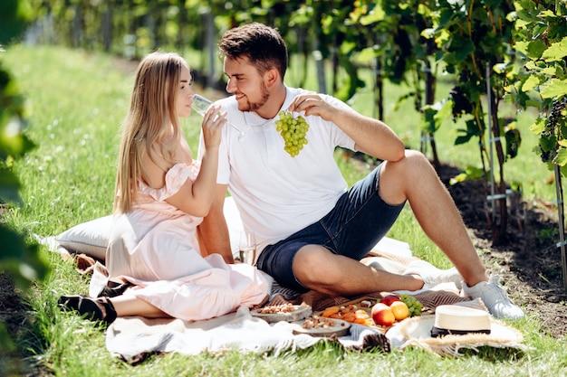 Fille amoureuse et garçon assis sur une couverture en train de manger des raisins et de boire du vin pendant un pique-nique dans le jardin de raisins