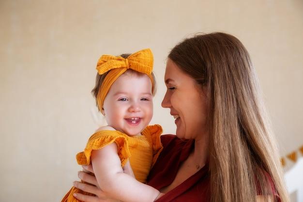 Fille d'un an en vêtements jaunes dans les bras d'une mère aimante, photo en studio pendant un an de l'enfant