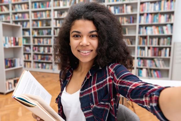 Fille d'angle élevé prenant selfie à la bibliothèque