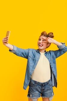 Fille d'angle élevé prenant selfie