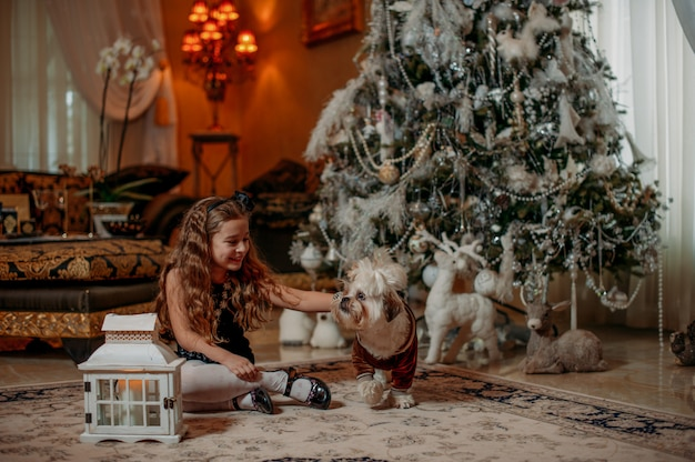 Fille avec un animal de compagnie avec arbre de noël