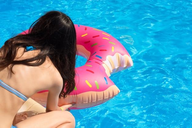 Fille avec anneau de bain gonflable en forme de beignet prêt à nager dans la piscine