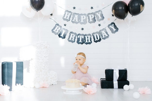 Fille d'anniversaire 1 an assis dans la zone photo entourée de cadeaux, de fleurs