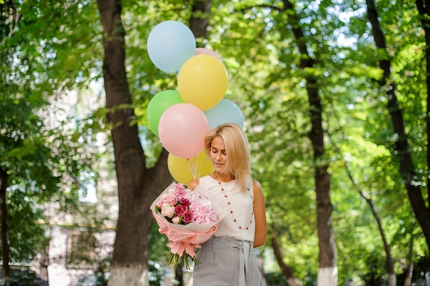 Fille d'anniversaire avec un bouquet de jolies fleurs et ballons