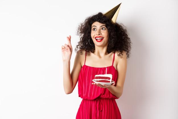 Fille d'anniversaire excitée faisant voeu, croiser les doigts bonne chance et regardant de côté le logo, célébrant bday, tenant un morceau de gâteau, fond blanc.