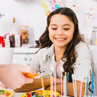 Fille d'anniversaire souriante regardant la main d'une personne allumant les bougies