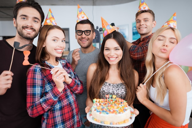 La fille d'anniversaire tient un gâteau avec des bougies.