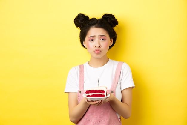 Fille d'anniversaire triste et solitaire fronçant les sourcils bouleversé, tenant le gâteau d'anniversaire avec bougie, faisant le souhait, debout sur le jaune.