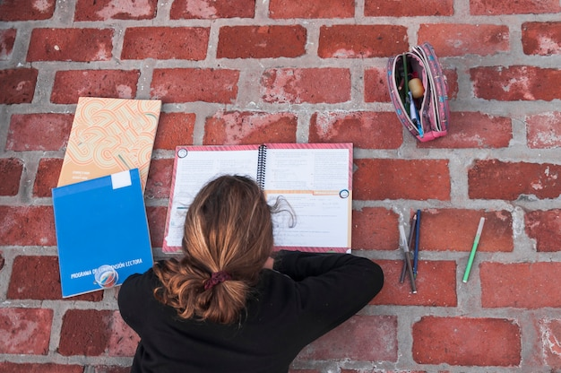 Fille anonyme étudie sur le trottoir de brique