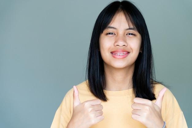 Fille de l'appareil dentaire souriant et regardant la caméra, elle se sent heureuse et a une bonne attitude avec le dentiste. motivez les enfants sans crainte lorsqu'ils doivent se rendre à la clinique dentaire.