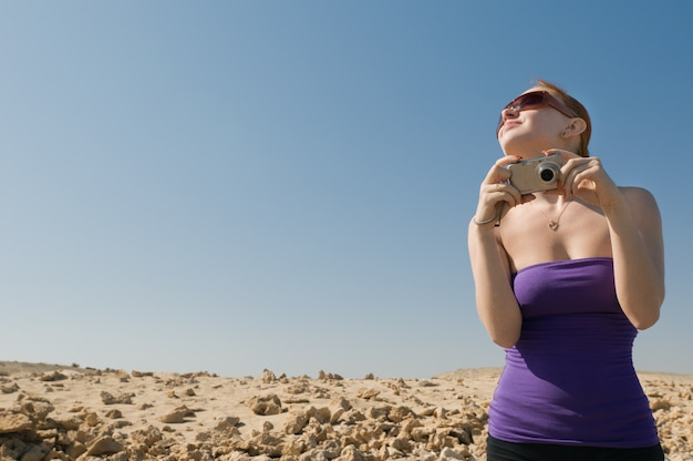 Fille avec appareil photo compact au désert