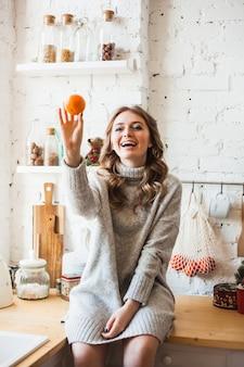 Une fille d'apparence européenne est assise dans la cuisine, jetant ou tenant des agrumes, de la mandarine, amusante et amusante, à la maison et cuisinant