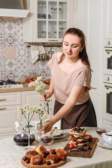 Une fille d'apparence européenne met la table à manger pour le petit déjeuner.