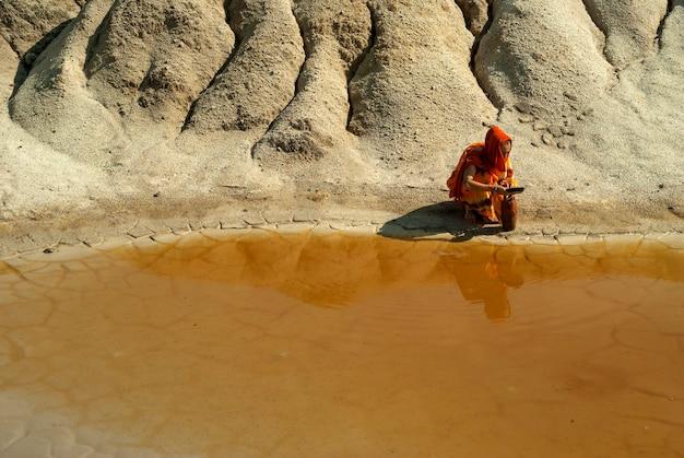 Fille d'apparence orientale en sari et hijab remplit le pichet d'eau dans la zone aride